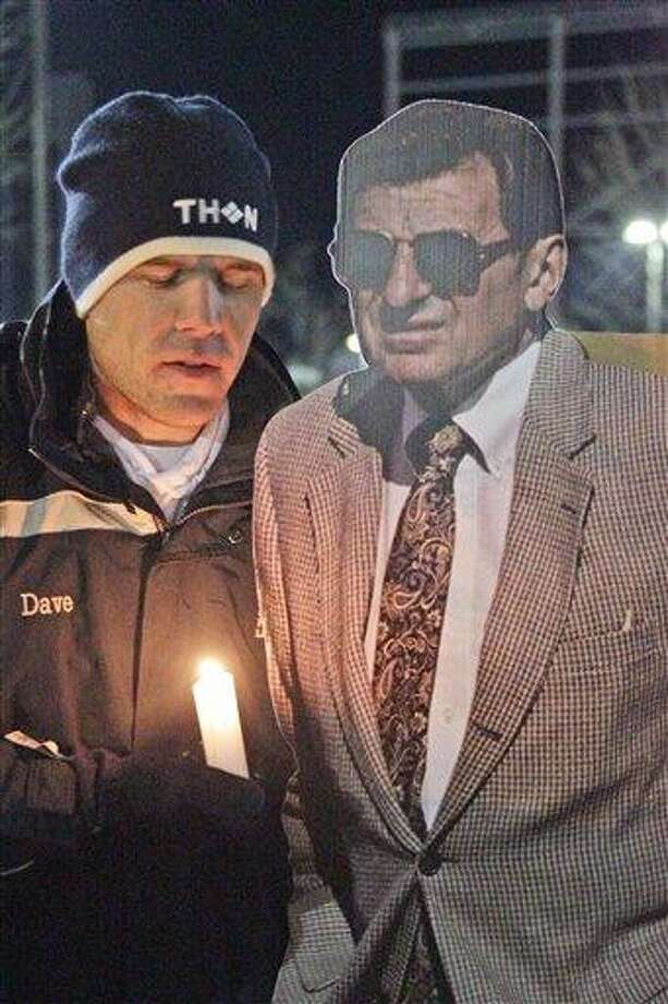 David Marselles, a senior at Penn State from Allentown, Pa., stands with a cardboard cutout of the late Joe Paterno near a statue of the former Penn State football coach, outside Beaver Stadium on the Penn State University campus Saturday in State College, Pa.  Associated Press Photo: AP / AP