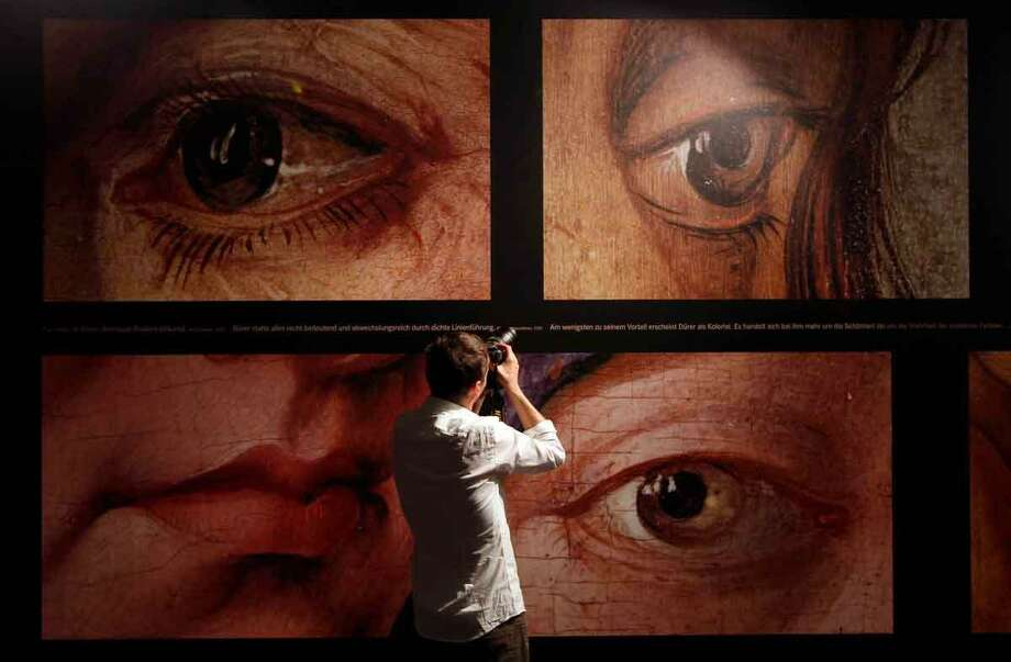 A man takes photos at the Albrecht Duerer exhibition during a press preview in the Germanisches Museum in Nuremberg, Germany, Tuesday, May 22, 2012. Germany's biggest exhibit of works by German artist Albrecht Duerer will open to the public from May 24 until September 2, 2012. (AP Photo/Matthias Schrader) Photo: ASSOCIATED PRESS / AP2012