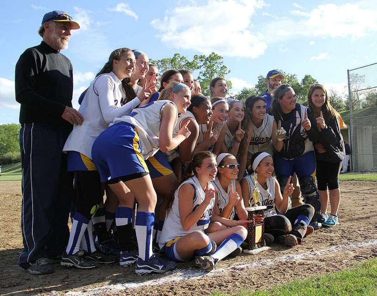 Joe Pelletier/The Middletown Press H-K softball coach Jeff Talbott, left, and his Cougars celebrate with the Shoreline Conference championship trophy Sunday in Westbrook. H-K defeated Morgan in nine innings, 3-2.