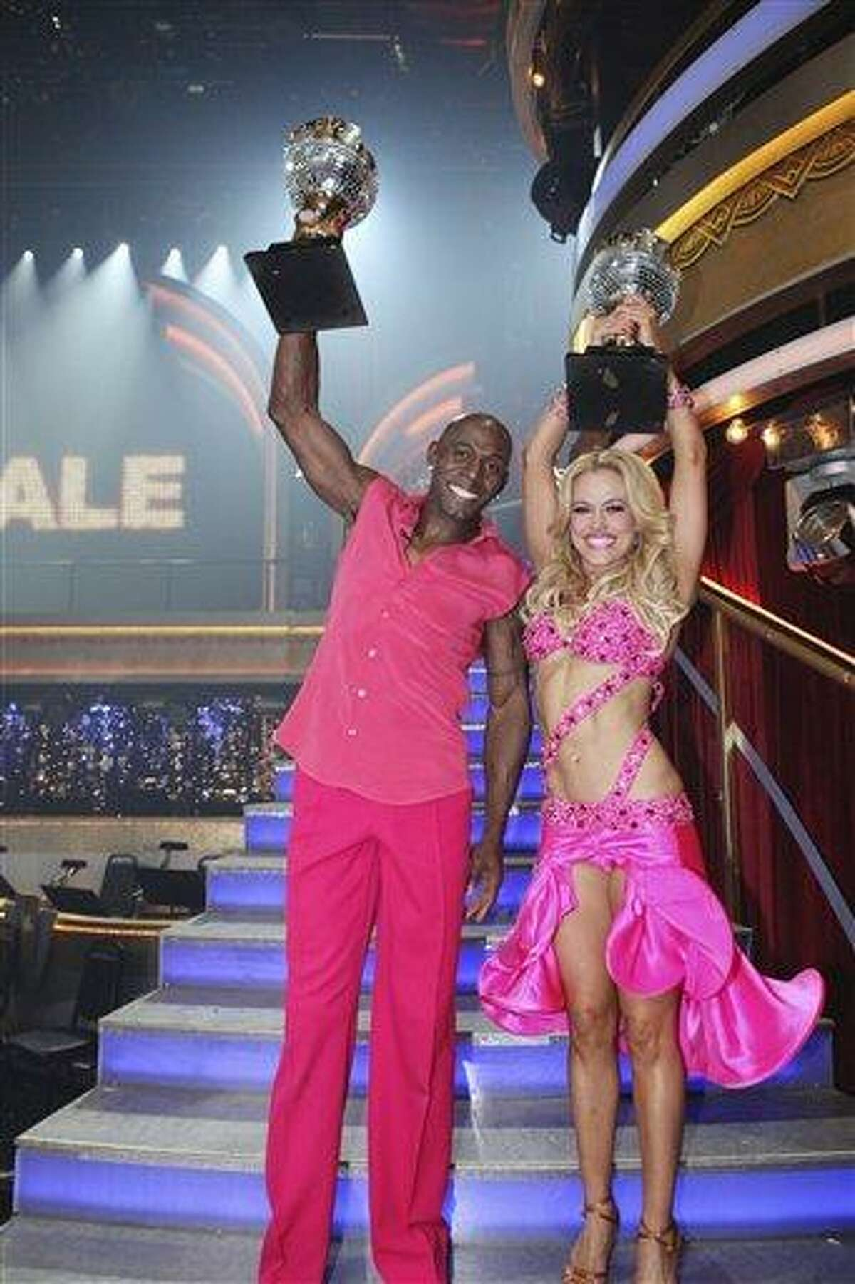 In a photo provided by ABC, Donald Driver and Peta Murgatroyd hold up their trophies after they were crowned