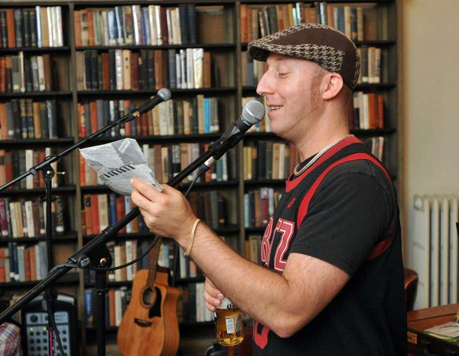 """Davy Rothbart, creator of """"Found"""" magazine, reads a found note at the Institute Library in New Haven during a talk there. Photo Peter Casolino/New Haven Register"""