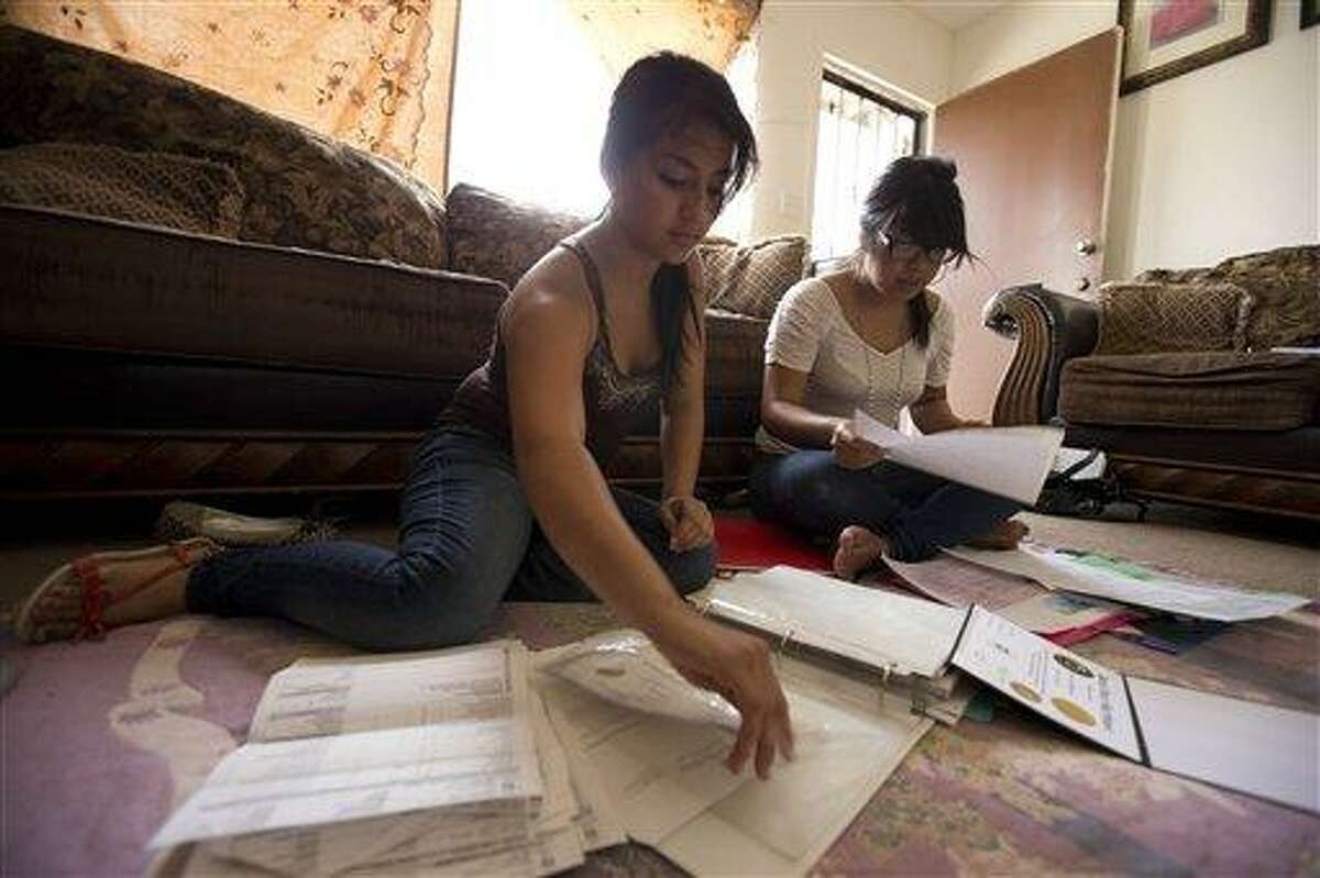 Itzel Guillen, left, sorts out some of the documents she needs to apply for a work permit along with Lucero Maganda, right, at her home Wednesday, Aug. 15, 2012, in San Diego. Guillen and Maganda are among those hoping for the right to work legally in America without being deported. (AP Photo/Gregory Bull)