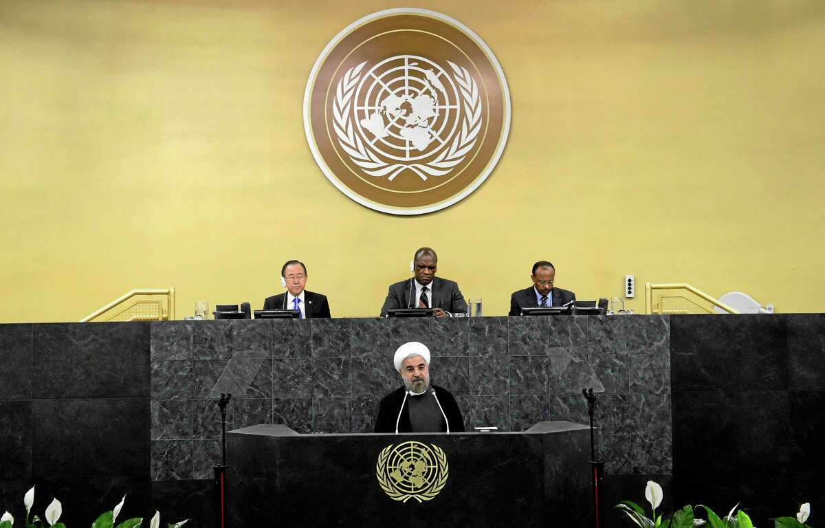 United Nations Secretary-General Ban Ki-moon, left, president of the 68th Session of the United Nations General Assembly John Ashe, center, and Under Secretary-General Tegegnework Gettu, right, are seated above as Iranian President Hassan Rouhani addresses a high-level meeting on Nuclear Disarmament during the 68th United Nations General Assembly on Thursday Sept. 26, 2013 at U.N. headquarters. (AP Photo/Mike Segar,Pool)