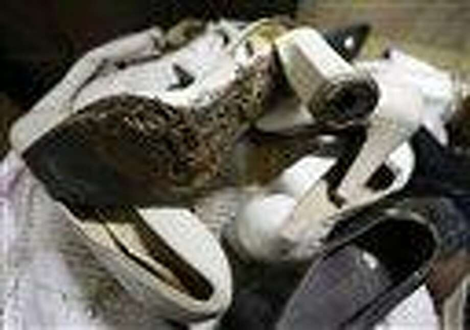 A branded high heel shoe, once worn by flamboyant former Philippine first lady Imelda Marcos sits among equally-damaged shoes in a section of the National Museum in Manila, Philippine. AP Photo Photo: AP / AP