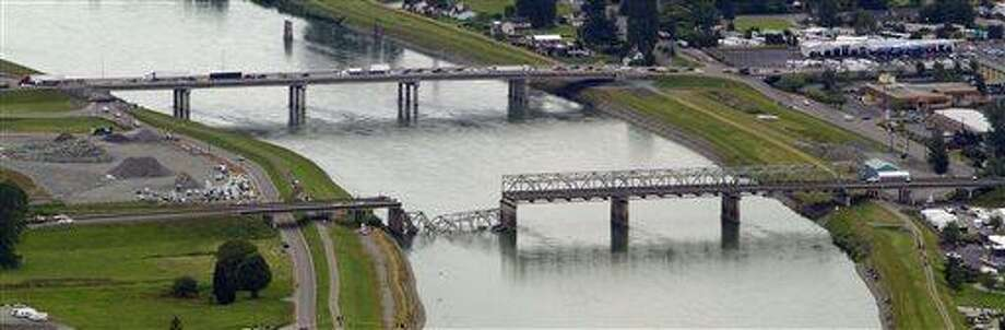 A collapsed section of the Interstate 5 bridge over the Skagit River is seen in an aerial view Friday, May 24, 2013, in Mt. Vernon, Wash. Part of the bridge collapsed Thursday evening, sending cars and people into the water when a an oversized truck hit the span, the Washington State Patrol chief said.  Washington Gov. Jay Inslee on Friday declared a state of emergency in three counties around the bridge, saying that the bridge collapse has caused extensive disruption, impacting the citizens and economy in Skagit, Snohomish and Whatcom Counties. (AP Photo/The Seattle Times, Mike Siegel) Photo: AP / The Seattle Times