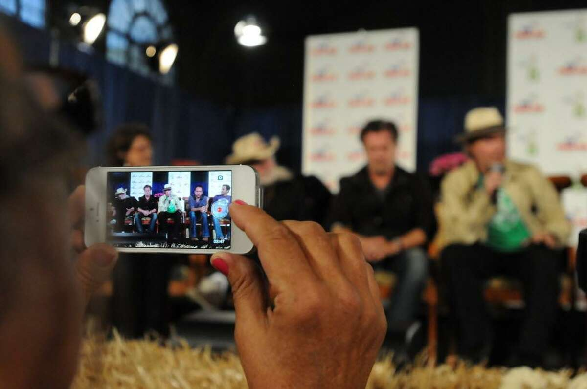 Using her iPhone, a photographer records the Farm Aid news conference Saturday in the old Hershey Museum at the west side of Hersheypark Arena. The concert performers on her screen are, from left, Willie Nelson, John Mellencamp, Neil Young, Dave Matthews and Jack Johnson. Jeremy Long/Lebanon Daily News
