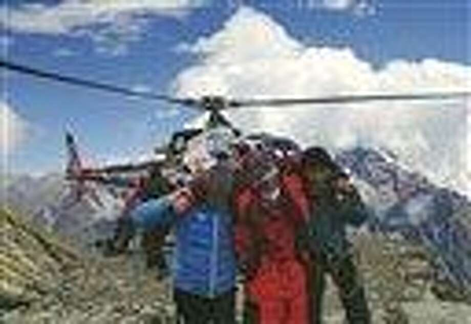 In this photo provided by Nepalese airline Simrik Air, an injured victim, center, of an avalanche is rescued at the base camp of Mount Manaslu in northern Nepal Sunday. The avalanche swept away climbers on a Himalayan peak, leaving at least nine dead and six others missing, officials said. AP Photo/Simrik Air Photo: AP / Simrik Air
