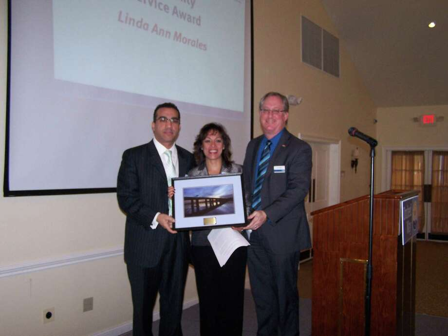 Linda Morales accepts the United Way Community Service Award from Kevin Wilhelm, United Way's executive director. Linda's brother John Paul Morales  poses with them. (Photo by Jim Salemi)