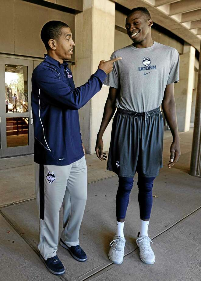 UConn head coach Kevin Ollie, left, talks with Amida Brimah prior to the annual Husky Run on Wednesday in Storrs. Ollie's son, Jalen, is a senior quarterback and Glastonbury and is demonstrating the same leadership abilities his father is famous for. Photo: Jessica Hill — The Associated Press  / FR125654 AP