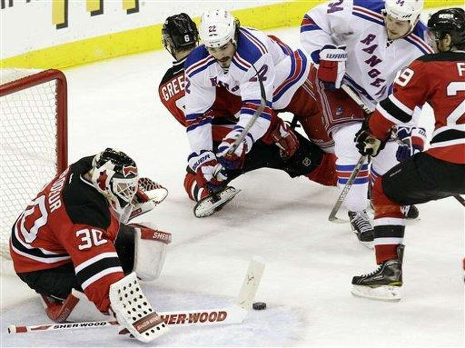 New Jersey Devils goalie Martin Brodeur makes a save as defenseman Andy Greene (6) holds back New York Rangers centers Brian Boyle (22) and John Mitchell in the third period during Game 4 of their NHL Eastern Conference Final series, Monday, May 21, 2012, in Newark, N.J. The Devils won 4-1. (AP Photo/Kathy Willens) Photo: AP / AP