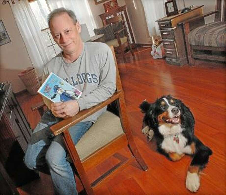 "Catherine Avalone/The Middletown Press  Retired Middletown Police Sergeant Craig M. Elkin in his Haddam home with his dog Nikita at his side. Elkin is the author of ""A Cop's Tale: Amusing Short Stories Written at the Expense of Others."""