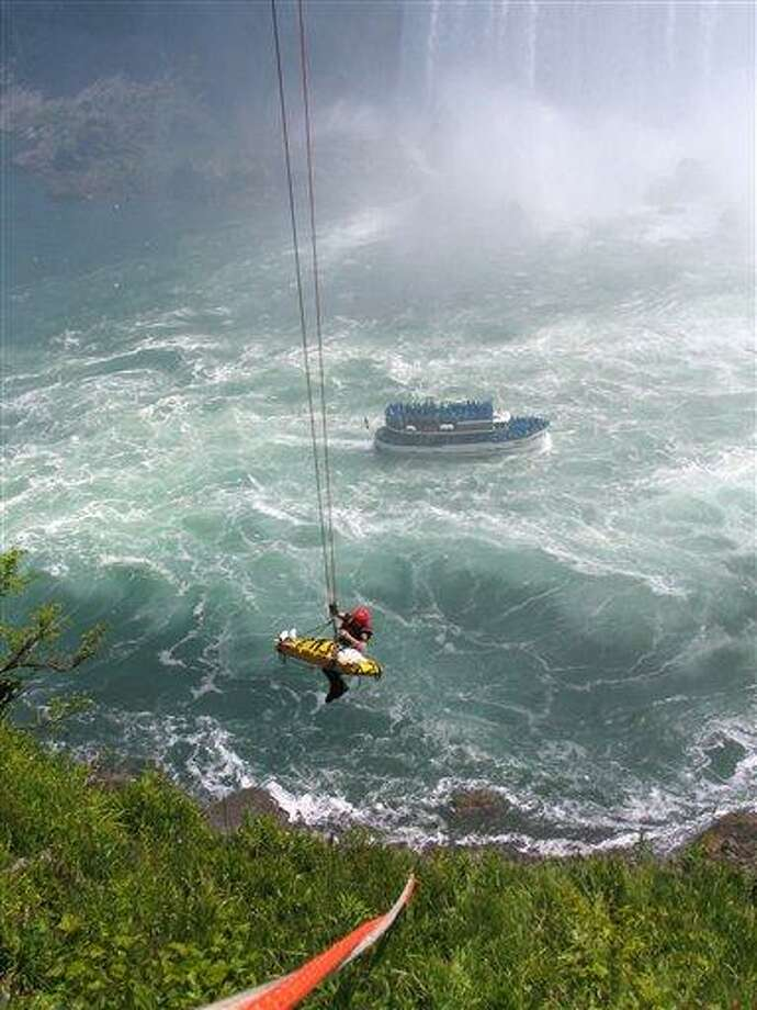 Niagara Falls emergency officials rescue a man who plunged over Niagara Falls and survived in an apparent suicide attempt, Monday. The man is only the third person known to have survived going over without a safety device. Associated Press Photo: AP / AP