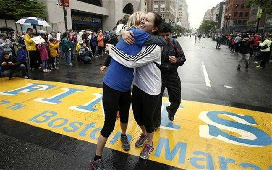Rachel, left, and Pam Vingsness of Newton, Mass., hug each other after crossing the finish line as runners who were unable to finish the Boston Marathon on April 15 because of the bombings were allowed to finish the last mile of the race in Boston, Saturday, May 25, 2013. (AP Photo/Winslow Townson) Photo: AP / FR170221 AP