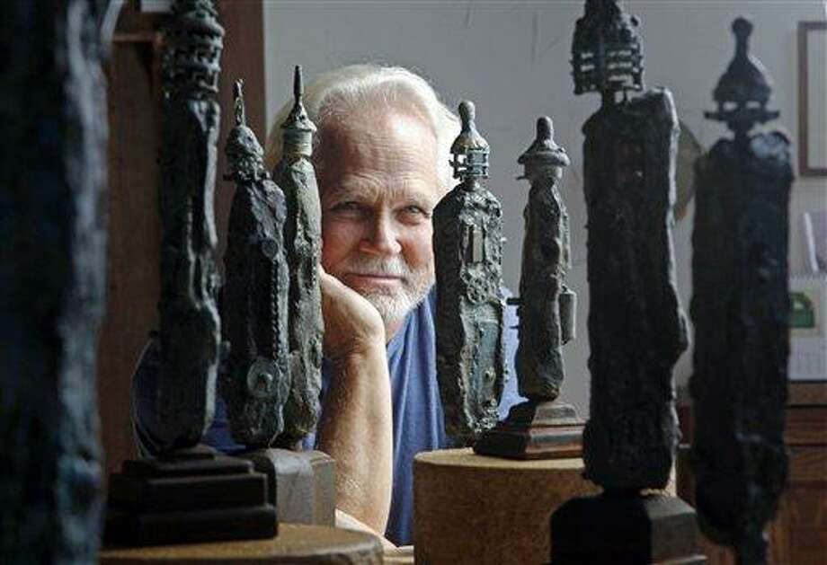 """In this Thursday, Sept. 18, 2012 photo, Tony Dow, actor, director and artist, poses with some of his works at his home and studio in the Topanga area of Los Angeles. When it comes time to sitting down in a studio and carving out bronze and wooden sculptures inspired by the nature all around him, Wally isn't leaving it up to the Beav these days. Dow, who famously played the Beaver's older brother Wally on the classic 1950s-60s sitcom """"Leave it To Beaver,"""" is carving out a name for himself in the art world these days, as an abstract artist. (AP Photo/Reed Saxon) Photo: AP / AP"""