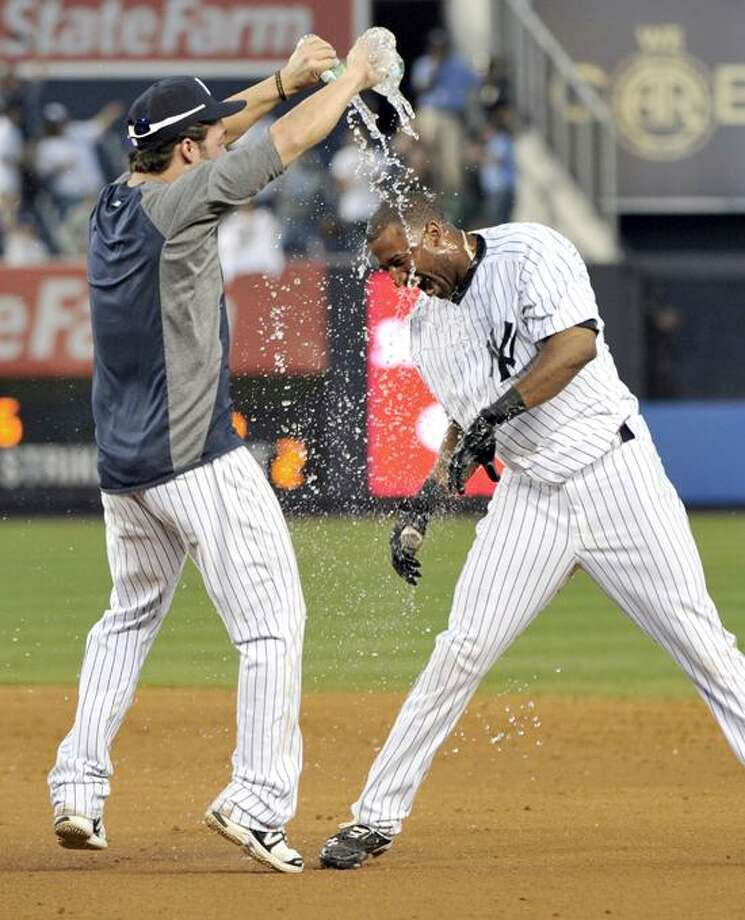 New York Yankees' Nick Swisher, left, douses teammate Eduardo Nunez with water after they defeated the Oakland Athletics 10-9 during the 14th inning of a baseball game on Saturday, Sept. 22, 2012, at Yankee Stadium in New York. (AP Photo/Bill Kostroun) Photo: AP / FR51951 AP
