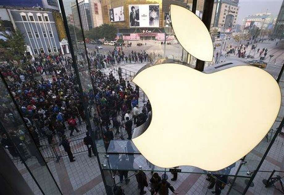 FILE - In this Oct. 20, 2012 photo, people line up to enter a newly-opened Apple Store in Wangfujing shopping district in Beijing. Apple's profit surge halted in the latest quarter, as a flood of new products like the iPhone 5 meant high start-up costs for new production lines. Apple posted net income for the October to December quarter that was flat with the year before. It was the first time in years that Apple didn't post a double-digit earnings increase. (AP Photo/Andy Wong, File) Photo: AP / AP