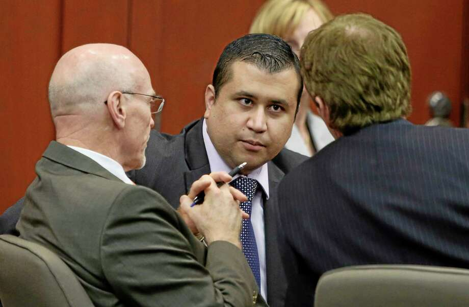"""In this Saturday, July 13, 2013. photo, George Zimmerman, center, speaks with his legal counsel, Mark O'Mara, right, and Don West during Zimmerman's second degree murder trial for the killing of Trayvon Martin in Sanford, Fla. Whether they think he got away with murdering 17-year-old Trayvon Martin or that he was just a brave neighborhood watch volunteer """"standing his ground,"""" many Americans can't seem to get enough of George Zimmerman. And he can't seem to stop giving it to them. (AP Photo/Orlando Sentinel, Gary W. Green, Pool) Photo: AP / Pool Orlando Sentinel"""