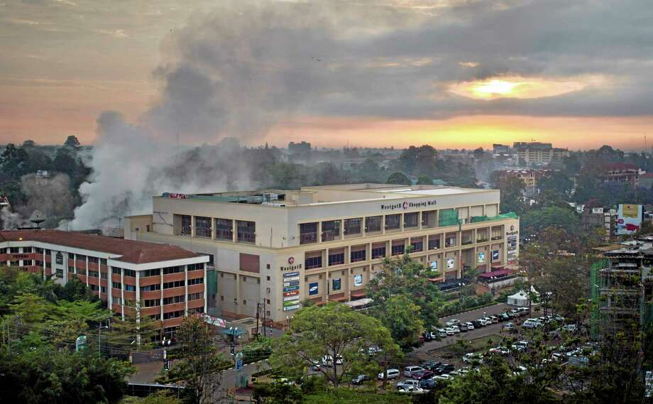 Dawn breaks over the still-smoldering Westgate Mall in Nairobi, Kenya, Thursday, Sept. 26, 2013. Working near bodies crushed by rubble in a bullet-scarred, scorched mall, FBI agents began fingerprint, DNA and ballistic analysis Wednesday to help determine the identities and nationalities of victims and al-Shabab gunmen who attacked the shopping center, killing more than 60 people. (AP Photo/Ben Curtis) Photo: AP / AP