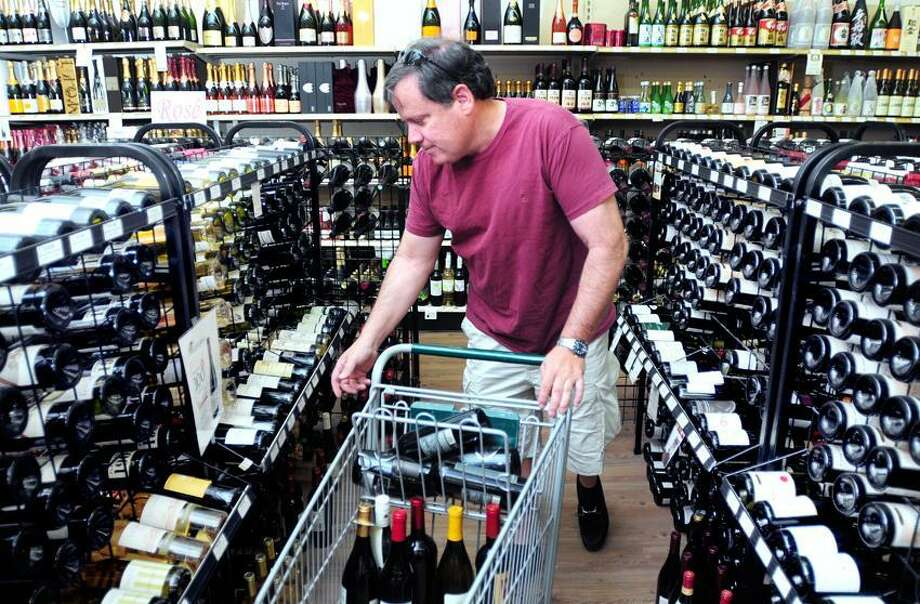 Joe Fields of Cromwell shops for wine at Amity Wine and Spirit in New Haven on Sunday. Arnold Gold/New Haven Register