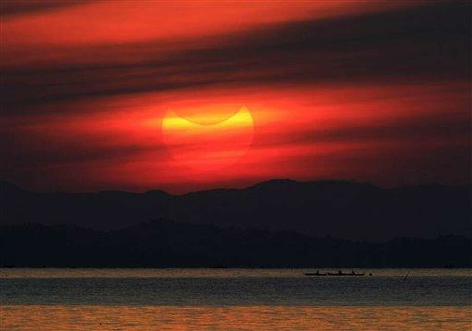 """An annular solar eclipse occurs as the moon passes between the earth and the sun as partially seen at sunrise Monday, May 21, 2012, from coastal township of Gumaca, Quezon province, 187 kilometers (116 miles) southeast of Manila, Philippines. Millions of Asians watched as a rare """"ring of fire"""" eclipse crossed their skies early Monday.  (AP Photo/Bullit Marquez) Photo: AP / AP"""
