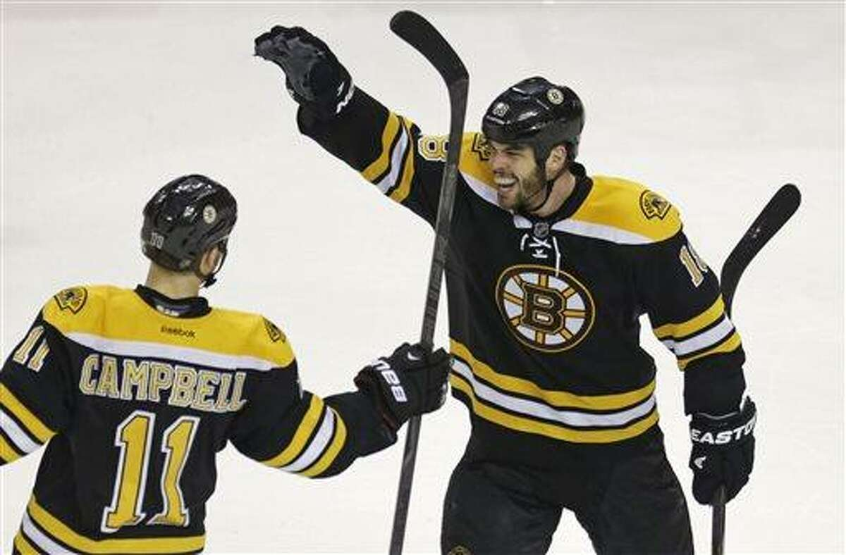 Boston Bruins center Gregory Campbell (11) is congratulated by teammate Nathan Horton, right, after his goal against the New York Rangers during the third period in Game 5 of the Eastern Conference semifinals in the NHL hockey Stanley Cup playoffs in Boston, Saturday, May 25, 2013. The Bruins won 3-1 and advance in the playoffs. (AP Photo/Charles Krupa)
