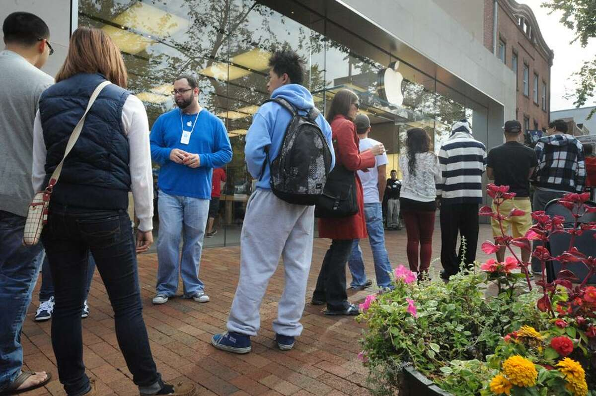 An Apple employee organizes early buyers waiting in line to get their iPhone 5 on its first day of sale at the Apple Store on Broadway at Yalein New Haven Friday. V.M. Williams/Register