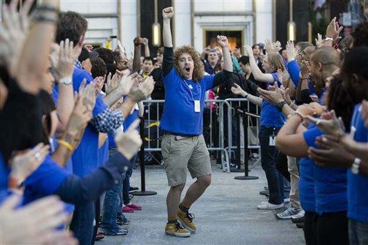 An Apple employee riles up his coworkers outside the Fifth Avenue Apple store to celebrate the release of the iPhone 5, Friday, Sept. 21, 2012, in New York. Hundreds of people waited in line through the early morning to be among the first to get their hands on the highly anticipated phone. (AP Photo/John Minchillo)