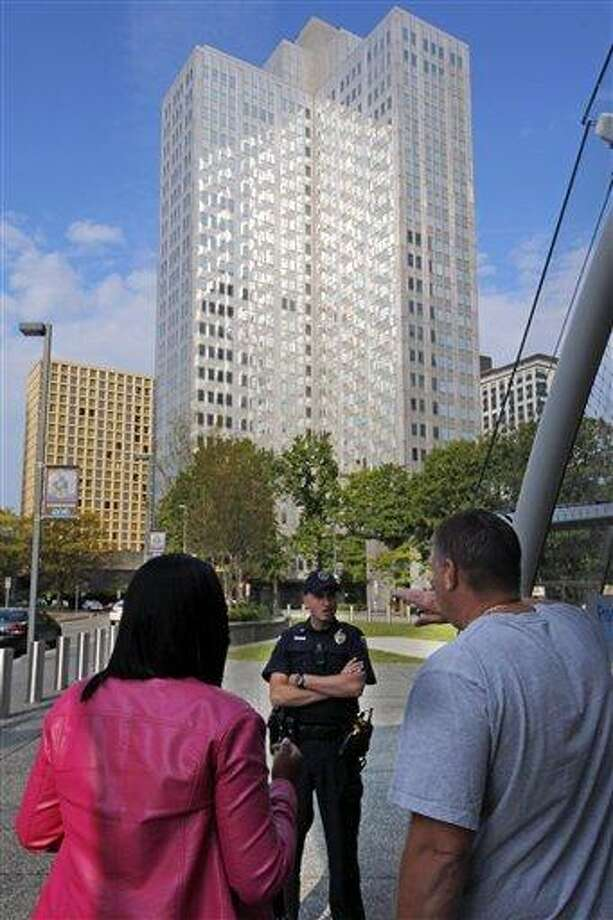 Police block off the area around Three Gateway Centeroffice building, rear, where they are negotiating with a man who claims to have a bomb, in downtown Pittsburgh Friday, Sept. 21, 2012. A call about an armed man inside the building prompted an evacuation amid reports of a hostage situation. (AP Photo/Gene J. Puskar) Photo: AP / AP