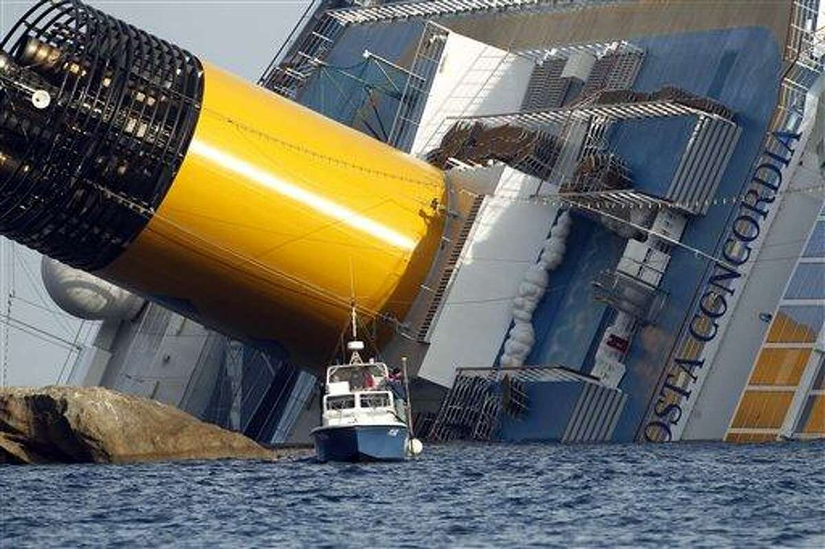 A police boat sails by the grounded cruise ship Costa Concordia, off the Tuscan island of Giglio, Italy, Sunday. Associated Press