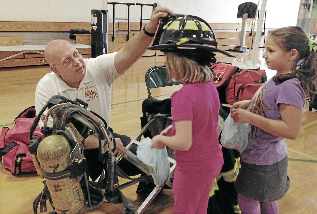 Middletown firefighter Gary Gessaro places a helmet on a second grader during Snow Elementary School's Career Day on Thursday. Kaitlyn Schroyer — The Middletown Press