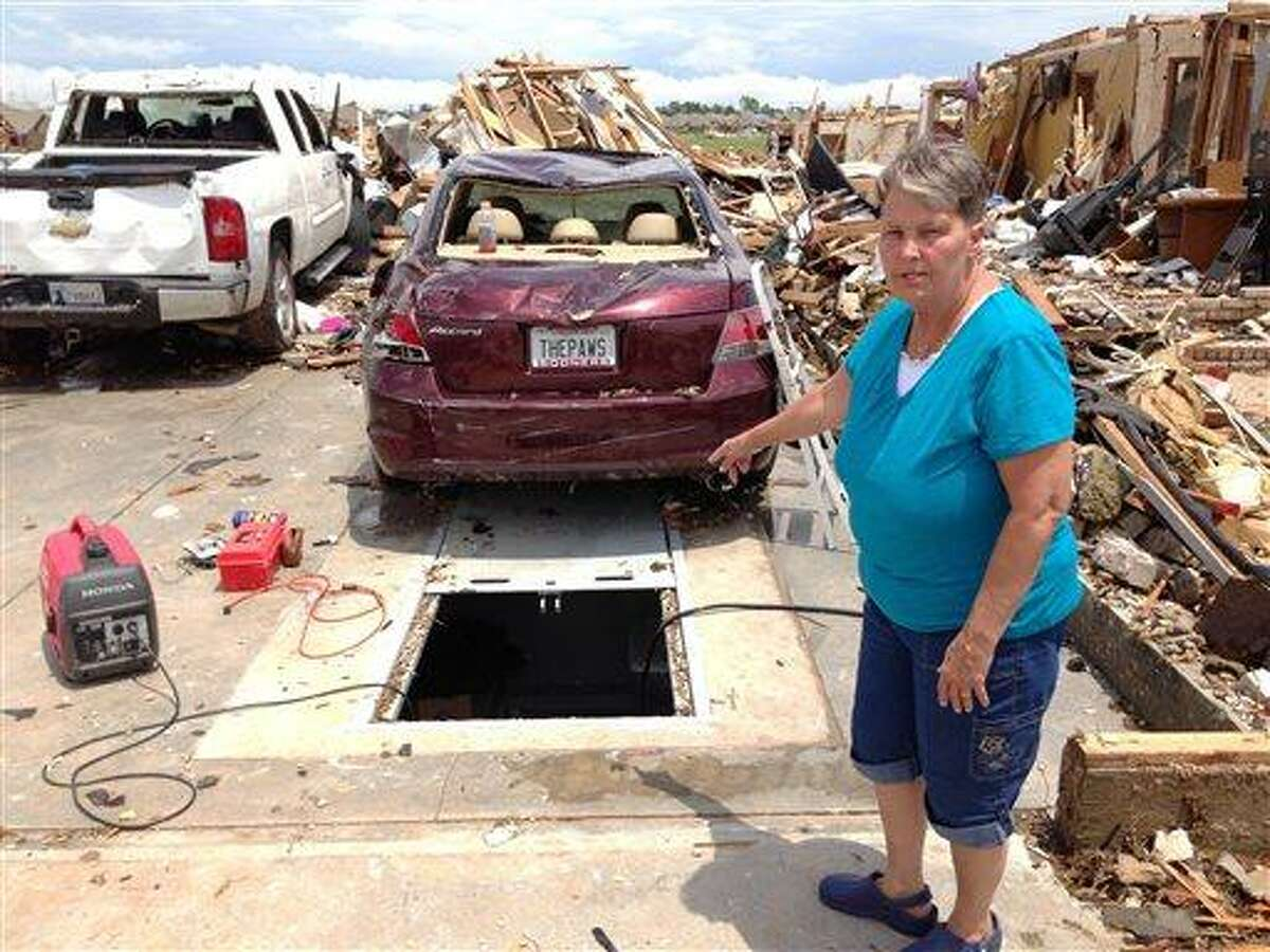 On Thursday, May 23, 2013 Sherry Wells stands near the storm shelter where she took cover when a tornado destroyed her home on Monday May 20, 2013 in Moore, Okla. Wells said she and her husband won a lottery draw to receive a government-subsidized rebate to install the storm shelter. A contractor finished work on the concrete bunker beneath the slab of their garage about three weeks before the tornado hit. (AP Photo/David A. Lieb)