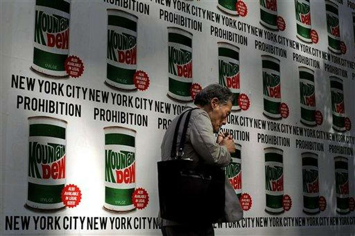 """A man lights a cigarette as he walks past an advertisement created in collaboration with Mountain Dew and New York Art Department, Thursday, Sept. 13, 2012, on 13th Street in New York. New York City cracked down on supersized sodas and other sugary drinks Thursday in what is celebrated as a groundbreaking attempt to curb obesity and condemned as a breathtaking intrusion into people's lives by a mayor bent on creating a """"nanny state."""" (AP Photo/Jeffrey Furticella)"""