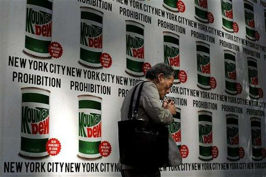 """A man lights a cigarette as he walks past an advertisement created in collaboration with Mountain Dew and New York Art Department, Thursday, Sept. 13, 2012, on 13th Street in New York. New York City cracked down on supersized sodas and other sugary drinks Thursday in what is celebrated as a groundbreaking attempt to curb obesity and condemned as a breathtaking intrusion into people's lives by a mayor bent on creating a """"nanny state."""" (AP Photo/Jeffrey Furticella) Photo: ASSOCIATED PRESS / AP2012"""