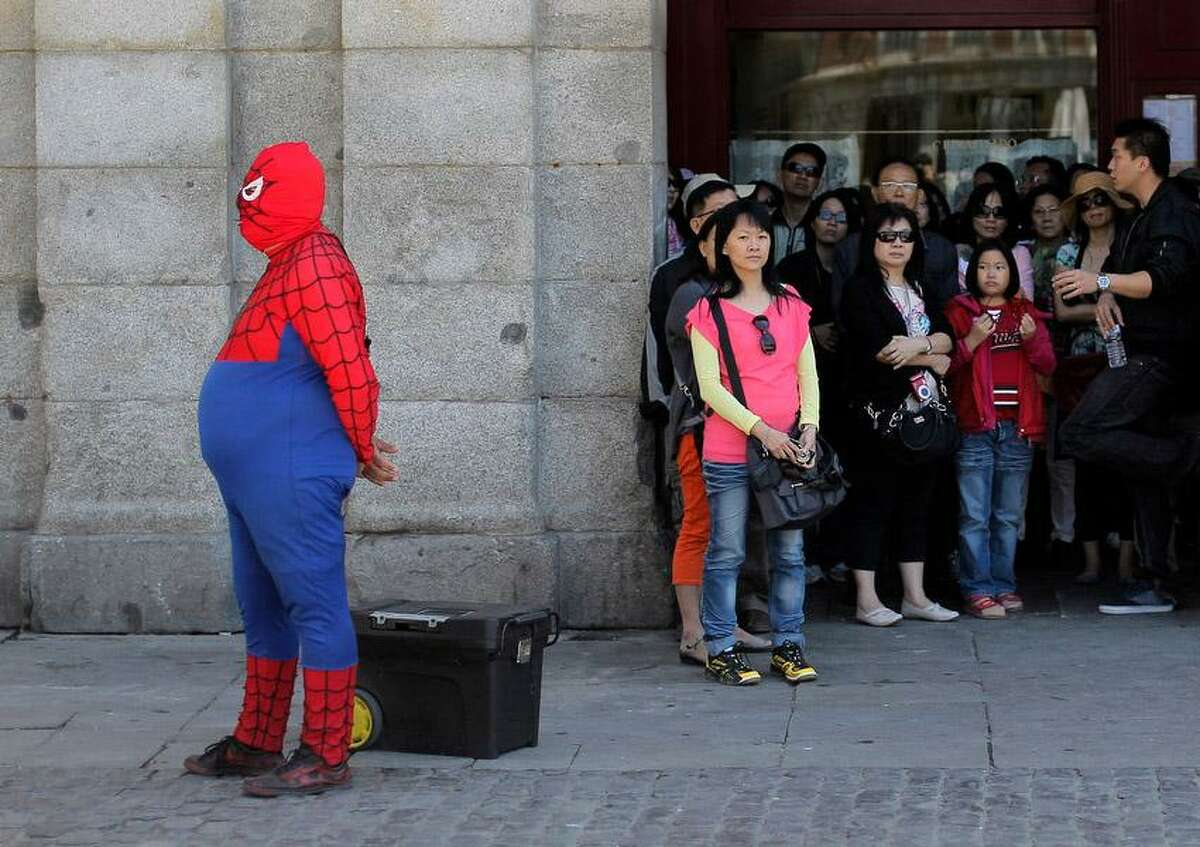 A man wearing a spiderman outfit performs for money as tourists look at the main square in Madrid, Spain, Thursday, May 23, 2013. Financial markets around the world were roiled Thursday after Japanese stocks suffered their biggest reverse since the tsunami that hit the country over two years ago. Spain has had to pay higher interest rates on selling euros 4 billion euros ($5.2 billion) in a bond auction that coincided with a sharp drop in global financial markets on worries over Chinaís economy. Spainís Ibex 35 stock index was down 2 percent. (AP Photo/Andres Kudacki)