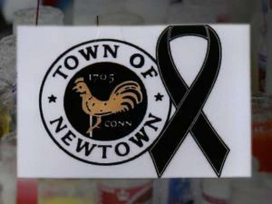A sign showing the town seal and a black ribbon is posted on the door of an antique colonial home in the historic district near the funeral for six-year-old student shooting victim Jack Pinto in Newtown, Conn., Monday, Dec. 17, 2012. A gunman opened fire at Sandy Hook Elementary School in the town, killing 26 people, including 20 children before killing himself on Friday. (AP Photo/Charles Krupa) Photo: AP / 2012 AP