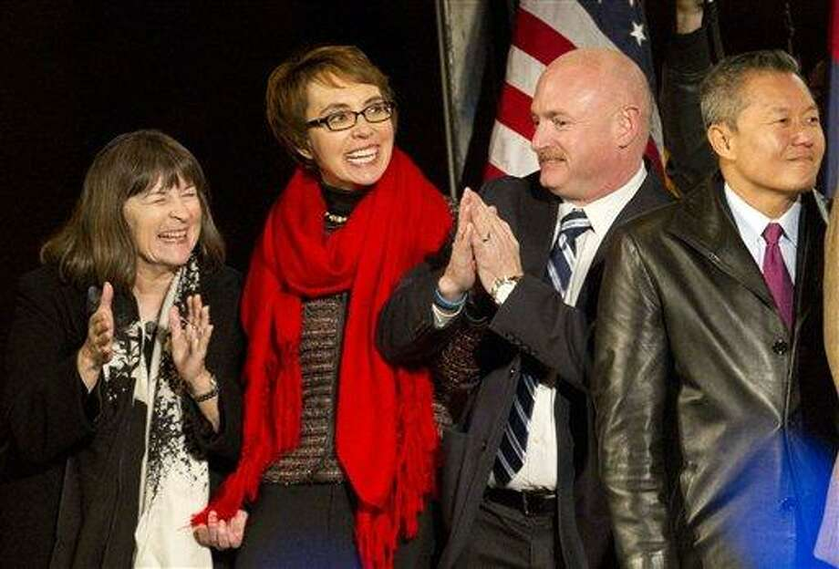 From left, Rabbi Stephanie Aaron, U.S. Rep. Gabrielle Giffords, her husband Mark Kelly, and University of Arizona Medical Center's Dr. Peter Rhee, dance to the music of Calexico, during a vigil at the University of Arizona in Tucson, Ariz., on Jan. 8. Giffords led a crowd in the Pledge of Allegiance in a rare public appearance one year after surviving a deadly shooting. Associated Press Photo: AP / The Arizona Republic