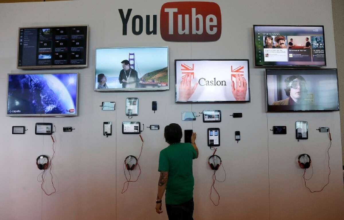 A man looks at a device a the YouTube booth at Google I/O 2013 in San Francisco.