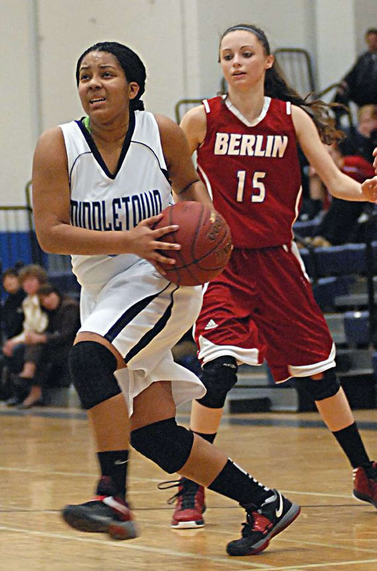 Catherine Avalone/The Middletown PressMiddletown junior forward Tamyia King drives to the hoop as Berlin guard Alicia Maule in Thursday night's game at the Labella-Sullivan Gymnasium in Middletown. The Redcoats defeated the Blue Dragons 57-51.