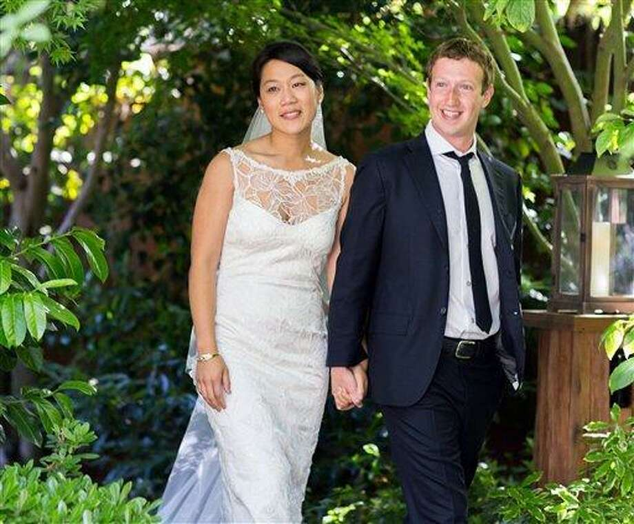 "This photo provided by Facebook shows Facebook founder and CEO Mark Zuckerberg and Priscilla Chan at their wedding ceremony in Palo Alto, Calif., Saturday, May 19, 2012. Zuckerberg updated his status to ""married"" on Saturday. The ceremony took place in Zuckerberg's backyard before fewer than 100 guests, who all thought they were there to celebrate Chan's graduation. (AP Photo/Facebook, Allyson Magda Photography) Photo: AP / allyson magda photography 2012"