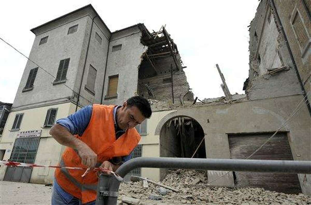 A volunteer ropes off the area surrounding a collapsed building in Finale Emilia, northern Italy after a quake hit northern Italy early Sunday. Associated Press