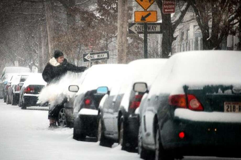Nicole Rodriguez cleans the snow from her car on Humphrey Street in New Haven. Melanie Stengel/Register