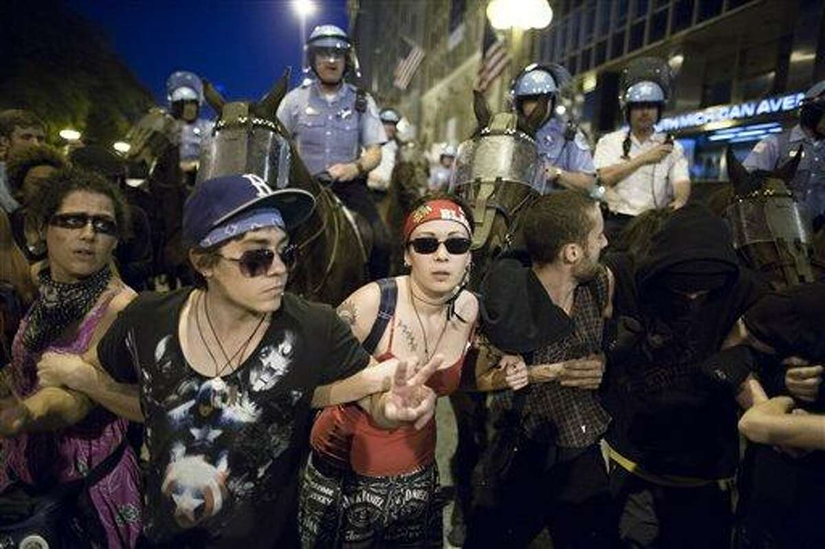Anti-NATO protesters form a barricade in front of mounted police officers during a march Saturday in Chicago. On Sunday, the start of the two-day NATO summit, thousands of protesters are expected to march to the McCormick Place convention center, where NATO delegates will be meeting. Associated Press