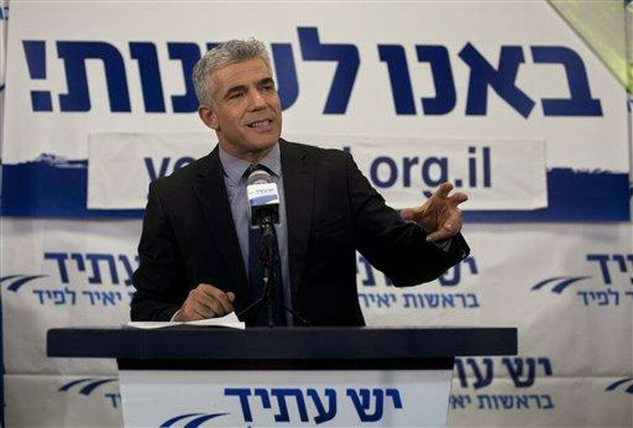 """Yair Lapid gestures as he delivers a speech at  his """"Yesh Atid"""" party in Tel-Aviv, early Wednesday, Jan. 23, 2013.  The party, formed just over a year ago, out did forecasts by far and are predicted to capture as many as 19 seats, becoming parliament's second-largest party, after Netanyahu's Likud-Beiteinu bloc, which won 31, according to the exit polls. (AP Photo/Sebastian Scheiner) Photo: AP / AP"""