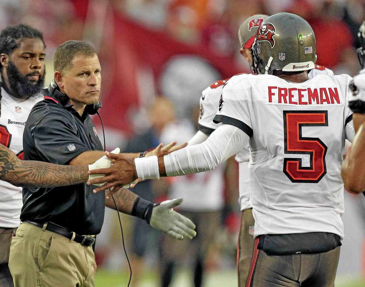 Buccaneers head coach Greg Schiano, left, shakes hands with quarterback Josh Freeman after Freeman threw a touchdown pass to wide receiver Kevin Ogletree during a Sept. 15 game against the New Orleans Saints in Tampa, Fla. The Buccaneers have benched Freeman and replaced him with rookie Mike Glennon. Wednesday's move came two days after Schiano insisted Freeman remained the starter because he gave the team the best chance to win.