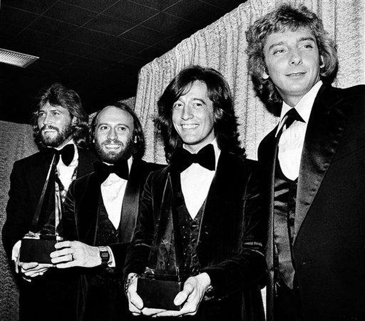 """In this Friday, Jan. 13, 1979 file photo, members of the Bee Gees pose with Barry Manilow, far right, at the American Music Awards in Los Angeles, Ca. The brothers Gibb, from left, Barry, Maurice, and Robin, won awards for favorite popular group and favorite soul album for """"Saturday Night Fever."""" A representative said on Sunday, May 20, 2012, that Robin Gibb has died. He was 62. (AP Photo/Nick Ut, File)"""