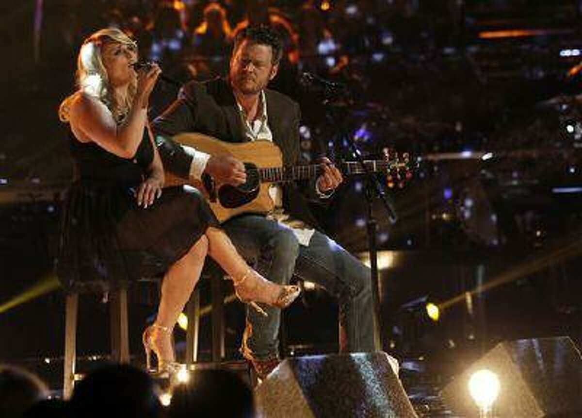 This May 21, 2013 photo released by NBC shows married singers Miranda Lambert, left, and Blake Shelton performing an acoustic version of the hit