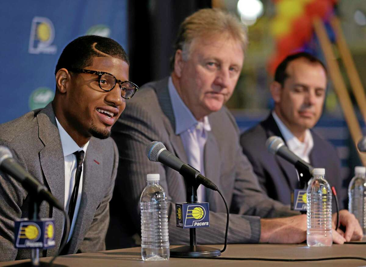 Pacers forward Paul George, left, talks about signing a multi-year contract extension with Indiana as team president Larry Bird, center, and head coach Frank Vogel look on Wednesday in Indianapolis.