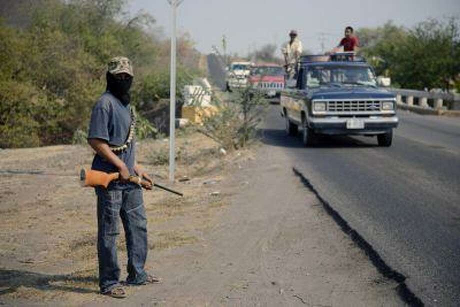 A member of the Community Police, a group of armed residents, stands guard on a check point at the entrance of Buena Vista Tomatlan in an operation to search for criminals in the zone called 'Tierra Caliente' in Michoacan State, Mexico on May 21, 2013. Photo: AFP/Getty Images / 2013 AFP