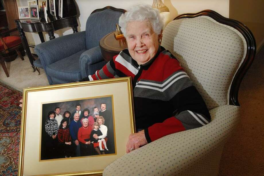 Catherine Avalone/The Middletown PressBarbara Hickey sits in the livingroom in her Middletown home with a portrait of her late husband, Paul Hickey and their six children; Jay, Phyllis, Maribeth, Charles, Kathleen and Christine. Christine will become the fourth Hickey sibling to be inducted into the Middletown Sports Hall of Fame joining Jay, Charles and Kathleen.