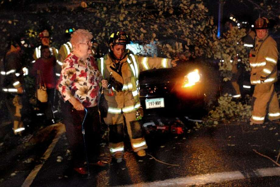 Marge Clancey, 91, of West Haven is helped away from the car where she was trapped. Clancey and her daughter Maureen Maddern were returning from a family celebration. When they stopped at the Winslow Drive stop sign, a section of a large tree fell on their roof. It took firefighters with chainsaws about 45 minutes to get them out. The tree landed on the supports behind the front doors. Melanie Stengel/Register